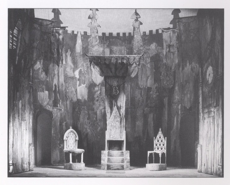 Black and white photograph of a set model showing three thrones of different designs.