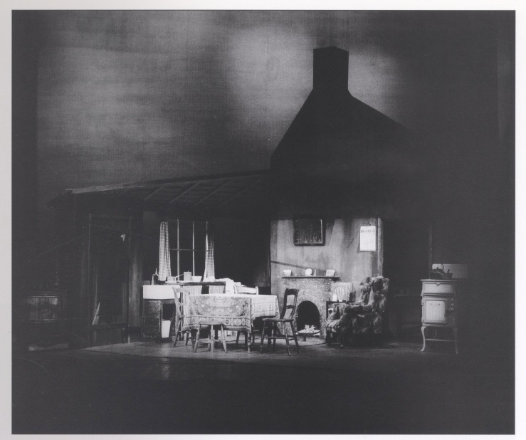 Photo of room with window and fireplace in background, table in centre with a wooden chair at either end and an armchair to the right. Above, the roof of the cottage is in shadow